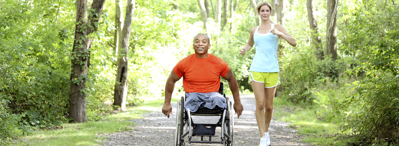 Man in wheelchair with Aquila wheelchair cushion and Woman running alongside